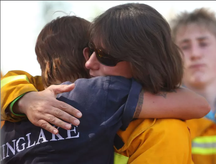 Australian volunteer firefighters from the Country Fire Authority comfort each other after a ceremony for the one-year anniversary of the Black Saturday bushfires, which killed 173 people. Picture: Lucas Dawson/Getty Images