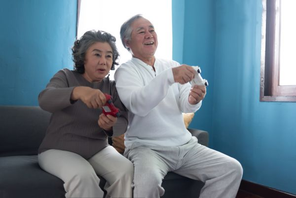 An elderly couple play video games