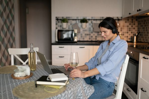 Woman drinking wine while working at a laptop