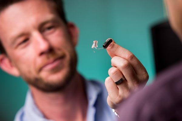 Man holding a hearing aid
